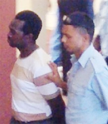 Clifton Anthony (left) being escorted by apoliceman.