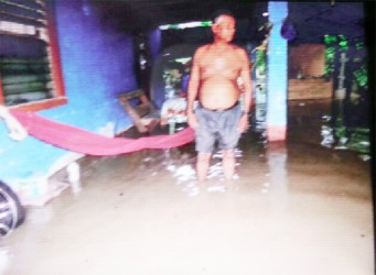 This man stands in floodwater after Hyde Park was hit by a high tide on Monday.