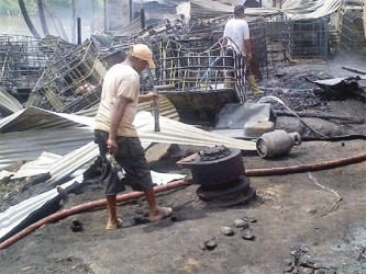 Residents going through the rubble of some of the buildings at Turn Basin, at the Port Kaituma waterfront in the aftermath of a fire started by a fuel boat explosion.