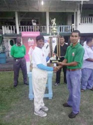 Captain of the winning Demerara team, Bhaskar Yadram receives the winning trophy from Sterlings Products representative Shane Cummings.