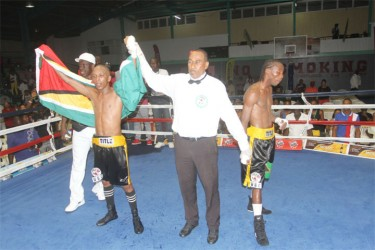 Dexter Marques' hands are raised by the referee along with his trainer, Lennox Daniels following his unanimous victory over Jamaican, Rudolph Hedge on Saturday.