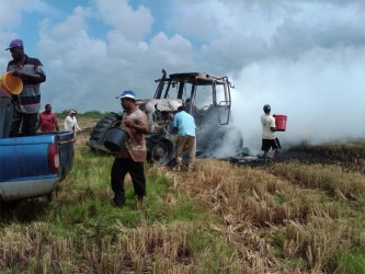 Persons trying to douse the burning tractor