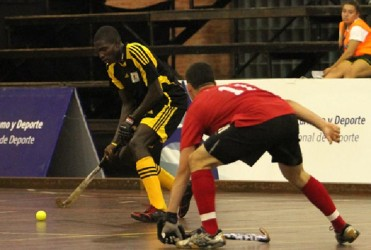 Guyana's Jamarj Assanah attempting to pass the ball while being challenged by USA's Williams Holt during their group matchup
