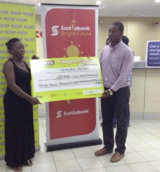 Tamika Miller (left) as she collected her one of her cheques from Marketing Manager of Courts Guyana, Pernell Cummings