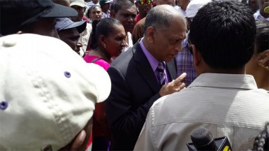 Minister of Agriculture Dr Leslie Ramsammy speaking to protesting sugar workers outside Parliament Buildings yesterday.