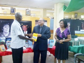 Deputy Vice-Chancellor Phillip DaSilva (left) formally receiving the collection from Sieyf Shahabuddeen while UG Librarian Gwyneth George looks on.