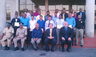 (From second left) Commissioner of Police Seelall Persaud, Minister of Home Affairs Clement Rohee, and US Ambassador Brent Hardt sit in front of the 21 graduates of the US Drug Enforcement Administration (DEA) airport interdiction course.