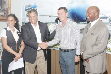 Roraima Airways' Chief Executive Officer Gerry Gouveia and Insel Air's Chief Commercial Officer Jurgen Lippinkhof shake after the signing of the ground handling contract between the two companies yesterday. With them are Roraima Airways' Debra Gouveia and Patrick Triumph. Roraima Airways is the General Sales Agent for Insel Air, which is entering the Guyana market.  (Photo by Arian Browne)