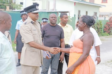 "A new start? Commissioner of Police Seelall Persaud shakes the hand of an Albouystown resident before the launch of the Guyana Police Force's ""Project Impact Albouystown"" yesterday afternoon. The new project will see the police force partnering with community organisations in a bid to make the community safe. (Photo by Arian Browne)"