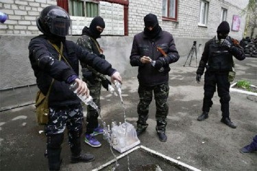 Masked men empty bottles of vodka to use them for petrol bombs in front of police headquarters in Slaviansk, yesterday. (Reuters/Gleb Garanich)