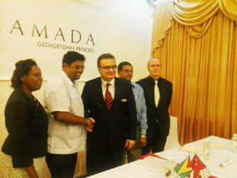Minister of Tourism Irfaan Ali shakes hands with General Manager, Princess International Hotel Jay Cunyet Dalcan, while Indranauth Haralsingh (behind Dalcan), Director of Tourism, Guyana Tourism Authority (GTA) and two other members of the Princess Hotel management team look on.