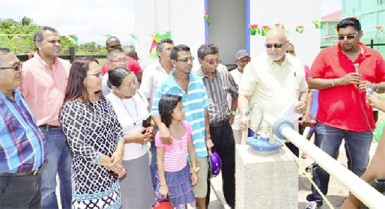 GWI's Chief Executive Officer, Shaik Baksh (third from right) President Donald Ramotar (second from right) and Housing and Water Minister Irfaan Ali (right) check the water flow from the newly commissioned Lethem well. (GINA photo)