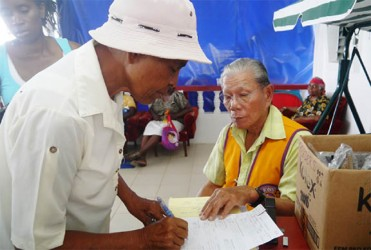 An elderly resident signs as she receives her free pair of glasses