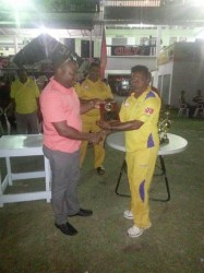 Everest Cricket Club President Stephen Lewis hands over several of the club's Centennial magazine to Preysal Captain.
