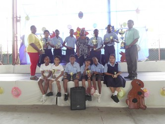 Trophy Stall representative Malenee Narine,centre along with Helena Ceasar, left and V Ouditt, head of Arawak Hose along with some of the prize winners at the Trophy Stall sponsored School of the Nations cricket competition which ended recently.