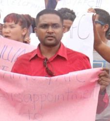 Permanent Secretary of the Amerindian Affairs Ministry Nigel Dharamlall holding a sign during a protest outside the Public Buildings last week. (Arian Browne photo)
