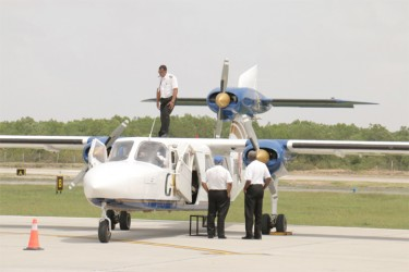 Prior to the flight Fields (right) does an inspection with Barclay (on top of the plane) and another pilot