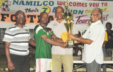 Director of Sport Neil Kumar hands over the second place trophy to the captain of the GDF team. (Orlando Charles photo)
