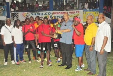 The Alpha United skipper receiving the first place trophy. (Orlando Charles photo)
