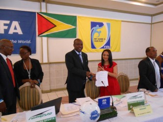 GFF President Christopher Matthias displaying the signed the four year kit contract along with Forward Sports International Incorporated Marketing and Sales Representative Juliet Osbourne.