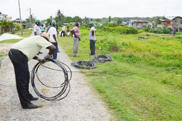 A GPL worker rolling up the illegal wires that were removed in Skull City (GINA photo)