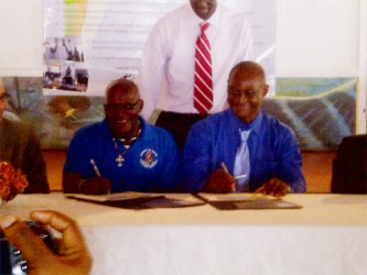 Uriel Dey (left) symbolically signing the declaration on behalf of New Amsterdam Mayor, Claude Henry. At right is Orrin Gordon, Chairperson, IMC Linden.