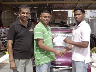 Benedict Prince (right) collects the cheque from Kevin Deodass of Motor Trend Auto in presence of the manager Jailall Deodass.