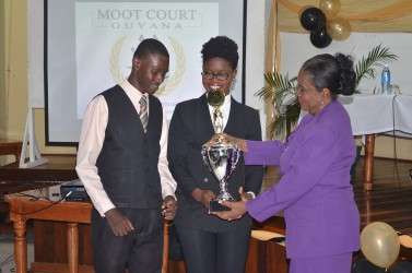 Dr. Carol Bishop (right) presenting the trophy for the Prof. Aubrey Bishop Annual Moot Competition to law students Sherrie Hewitt and Kevin Morgan   at the Moot Court Guyana exhibition held at the university's Education Lecture Theatre yesterday. (GINA photo)