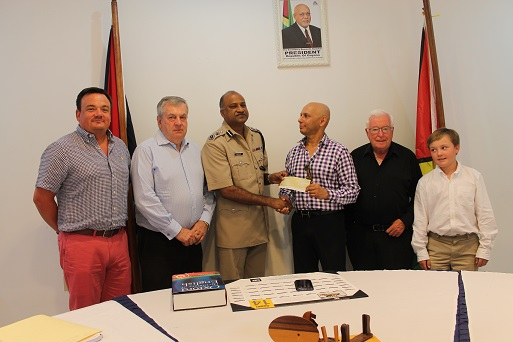 Dean Hassan (third from right) presenting the cheque to the acting Commissioner while other company investors look on. The child is the son of one of the investors. (Police photo)