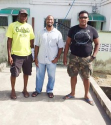 From left: Contractor  Malcolm Andrews of Vision Construction Company, which would be effecting repairs to the building, employee of the US Embassy Michael Fraser and GWMO member Hector Broomes stand in front of the building after Sunday's clean up.