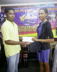 Ms. Kesheka Washington of Star Party Rental hands over the cheque to Bendict Prince of Quest International.