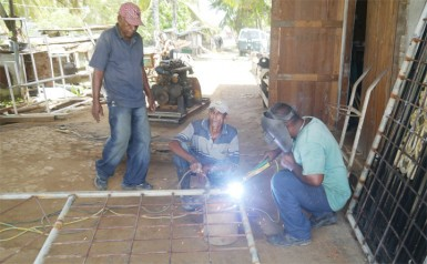 Rudy, welding his gate as Inshan Jameer and another friend look on
