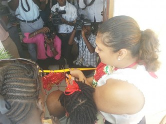 Minister of Education Priya Manickchand cutting the ribbon at the opening ceremony.