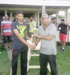 Shameer Sahib, vice chairman of the Enmore Cricket Club hands over the second prize to Lusignan's captain.