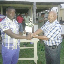 Tejnauth Jadunauth, Chairman of the Enmore Cricket Club hands over the prize which was sponsored by Trans Pacific and Woodpecker to Nichosie Barker.
