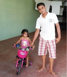 Little Sariah Persaud riding her bike with Stefan Harinauth watching out for her