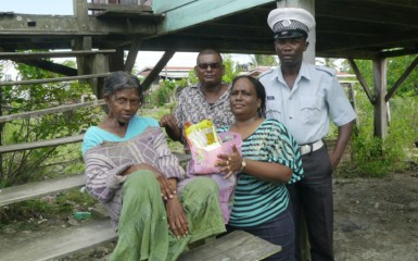Sergeant Cynthia Kelly and another officer presenting a hamper to a Bush Lot woman, 'Lettice.'