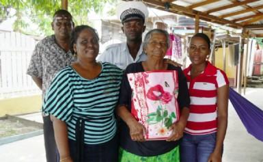 An elderly Bush Lot woman, Sookdai Rajkumar receives her food hamper from Sergeant Cynthia Kelly (left) and other officers.