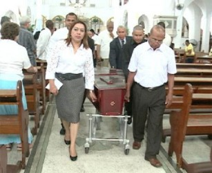 Foreign Affairs Minister Carolyn Rodrigues-Birkett (left) and John Rodrigues (brother of the deceased) along with others bear the casket of  the late Basil Rodrigues out  of the Brickdam Cathedral  (GINA photo)