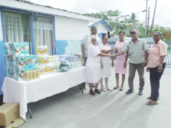 Food for the Poor (Guyana) Inc donated a number of items to the Chest Clinic of the Georgetown Public Hospital Corporation recently. Nurse in charge of the clinic, Sursattie Rajcumar said that the charity has been donating items to the clinic for about five years, according to a press release. The items are very useful to the nurses and to the patients, she said, and commended the organisation for its continuous support to the health sector. The charity's PR Manager, Wayne Hamilton, said it is cognisant of the needs of the health sector and the difficult conditions that nurses operate under daily, and pledged to lend support whenever possible to the hospital. In picture: Hamilton (second from right) shares a handshake with Rajcumar while other representatives look on.  The items are displayed on a table at left.