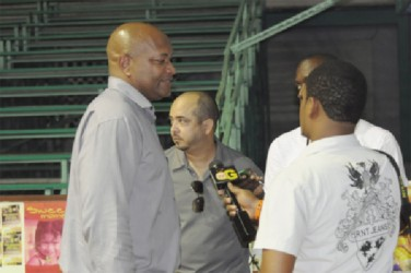 GABF President Nigel Hinds (left) speaking to the media in the presence of federation Vice President Michael Singh (centre) after gaining entry to the Cliff Anderson Sports Hall