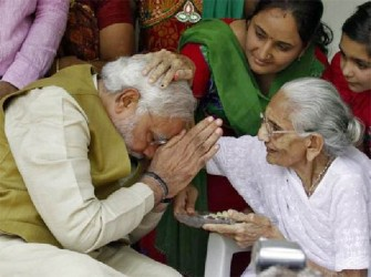 Hindu nationalist Narendra Modi, the prime ministerial candidate for India's main opposition BJP, seeks blessings from his mother Heeraben at her residence in Gandhinagar in the western Indian state of Gujarat May 16, 2014. REUTERS/Amit Dave