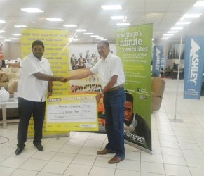 Tourism Minister Irfaan Ali receives the $2 million cheque from Managing Director of Courts Guyana, Clyde De Haas