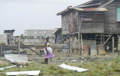 Beryl Thomas standing among the ruins
