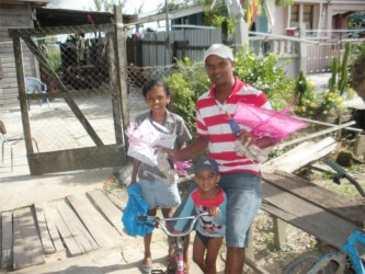 Narisa Alleyne (left), Kapaldil Kissoon (middle) and Ramnarine Ramdihall preparing to fly their kites left over from Easter.