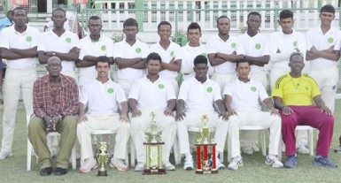 "A victorious Demerara team pose with manager Robert ""Pacer"" Adonis (left front row sitting) and Coach Garvin Nedd (far right front row sitting)"