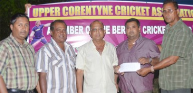 Mr. Shamnarine Narine proprietor of GUYTRAC hands over the sponsorship cheque to UCCA president Mr. Dennis De Andrade. Also in photo are Mr. H.N. Sugrim and other executives of the UCCA.