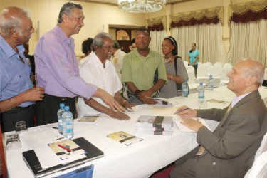 Former Chairman of Demerara Distillers Limited, Dr Yesu Persaud signing copies of his autobiography `Reaching for the Start; The Life of Yesu Persaud Vol 1' at its launching yesterday at the Pegasus Hotel. The first volume is an introduction to Persaud's life from his early childhood to his school days and ends in 1976.