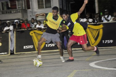 Threon Petre (left) of BV-B attempting to keep possession of the ball while being challenged by his Melanie-B marker during his side's semi-final win