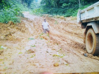 A driver standing in the depth of the eroded Mahdia Road